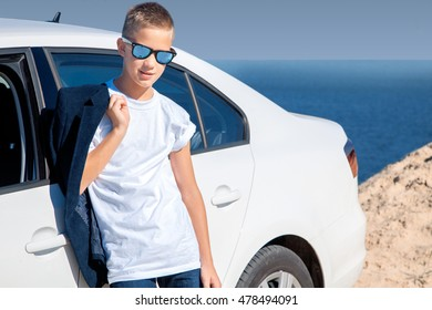 young boy in sunglasses looking at the camera at the beach near a white car