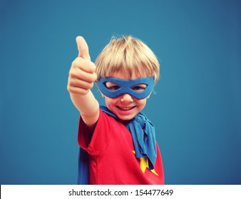 A young boy superhero giving you a thumbs up