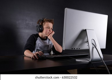Young boy surfing or playing games or studying on computer in headphones with microphone