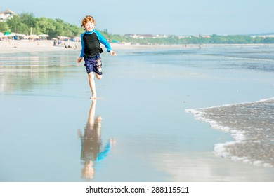Young boy in swimming shorts and rushwest runs along Bali beach near sunset with reflection in the water