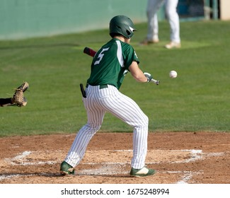 Young boy swinging the bat for a hit in baseball game