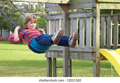 A young boy swinging on an outdoor swing.