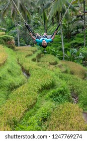 Young Boy Swinging Over the Tegalalang Rice Fields in Ubud, Bali, Indonesia