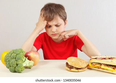Young boy at the table chooses between fastfood and vegetable and fruits on a white background