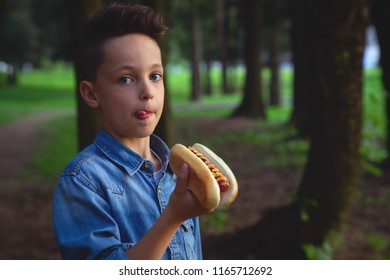 a young boy takes a bite of a hot dog in park