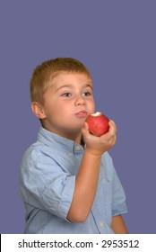 Young boy taking a bite out of a fresh apple