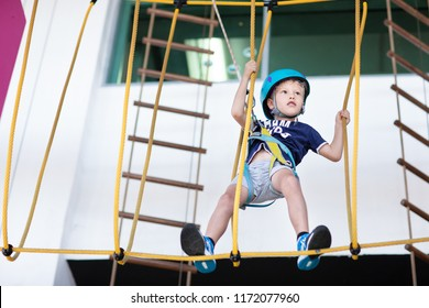 Young boy taking the challenge at the indoor high rope course