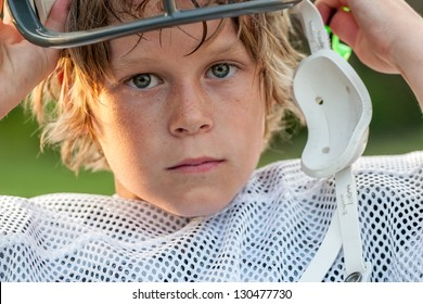 Young boy taking his football helmet off after a game
