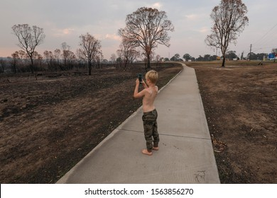 Young boy taking photos of land burnt out by bush fires in New South Wales, Australia. Australian fires 2019.