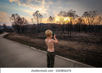 Young boy taking photos of land burnt out by bush fires in New South Wales, Australia