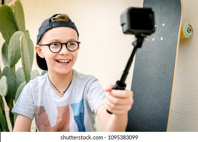 Young boy taking selfie on action camera outdoor with a skateboard and a cactus in background. Caucasian pre teen playing with action cam in the garden. Beautiful kid with hat and glasses smiling.