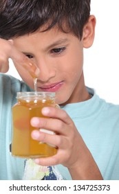 Young boy tasting some honey