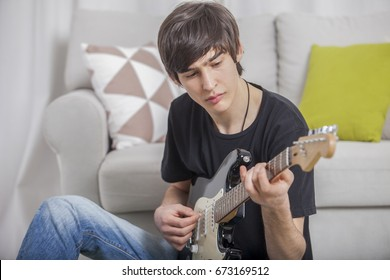 Young boy teenager in a children's room writes and composes a song on a guitar