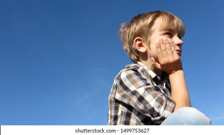 Young Boy Thinking / Dreaming / Getting Bored Outside Under Blue Sky, Copy Space Background