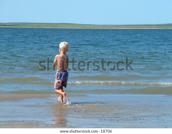 A young boy thrives on the beach.