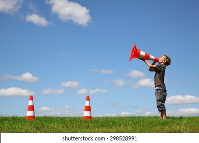 Young boy with traffic cones on a green meadow