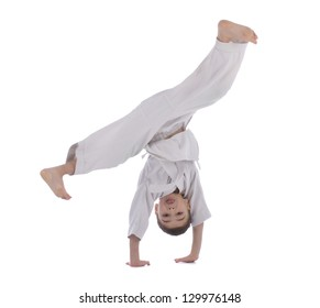 Young boy training acrobatic in kimono isolated on white background