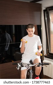 Young boy training indoors on bicycle stationary trainer with weights during pandemic, social distancing - isolation