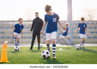 Young Boy Training Sports in Sunny Summer Day. Happy Kids Practicing Soccer on Schoolyard. Young Coach With Children Football Players on Training Session. Sports Stadium Seats in the Background