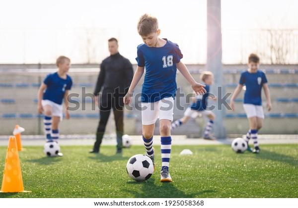 Jóvenes entrenando deportes en el soleado día de verano. Niños felices practicando fútbol en el patio de la escuela. Joven entrenador con niños jugadores de fútbol en sesión de entrenamiento. Asientos de estadio deportivo en segundo plano