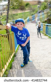 Young boy in a trendy blue outfit pausing for a rest on steep flight of outdoor stairs on a rural hillside leaning on the rail and grinning up at the camera