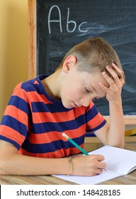 Young boy tries to do his homework. The problem with learning