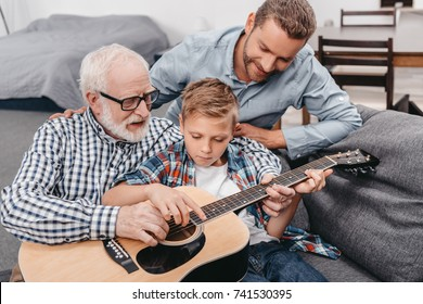 Young boy trying to learn playing guitar while his father and grandpa are helping him