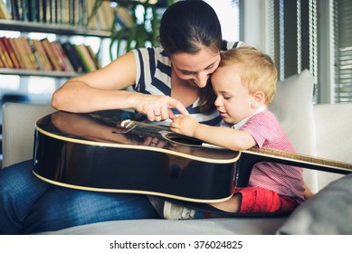 Young boy is trying to play guitar, mother is watching him