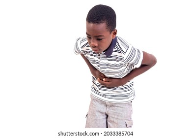 young boy in t-shirt bent over white background touching belly with hands feeling stomachache.