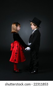 young boy in tuxedo and girl in red dress holding hands and looking at each other
