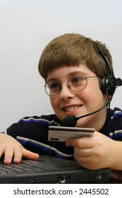 young boy using computer and credit card vertical