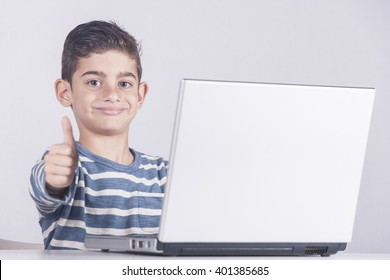 Young boy using a laptop computer (e learning concept). Toned image with selective focus
