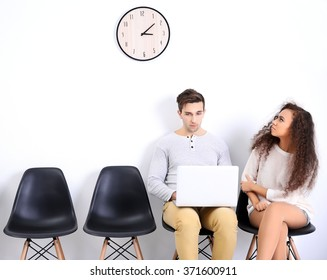 Young boy using laptop and woman looking at the clock in white hall