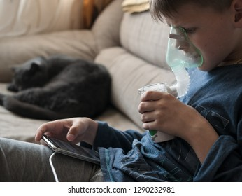 Young boy using nebulizer for asthma and respiratory diseases at home. Teenager doing inhalation inhales couples containing medication. Concept of home treatment. Medical procedures.