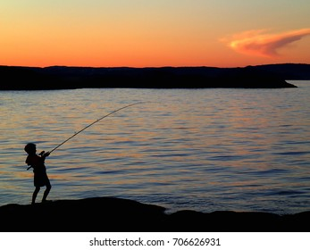 Young boy vatching a fish in the beautiful summer sunset.