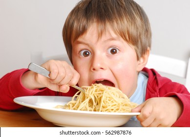 Young boy is very hungry, eating noodles very greedy