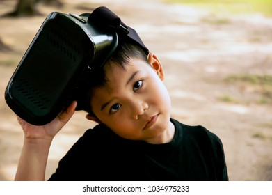 Young boy with VR headset in the garden, asian pretty boy, play with imagination. New activity for kid in this generation. High technology make everything easy and possible, reality as see.