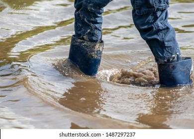 Young boy wading through high tide with blue gumboots after a flood has broken the protecting dike and overflowing the netherlands