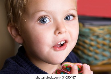 Young boy waiting at the kitchen table to taste newly decorated cookies