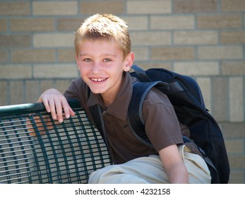 young boy waiting on a bench for the school bus