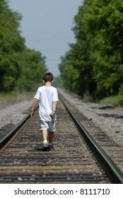 Young boy walking down railroad tracks in summer.