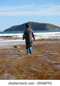 Young boy walking down river towards ocean