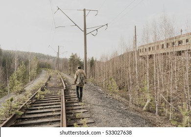 young boy walking on railroad tracks. He is holding the gun. wandering boy. man in a protective cloak with a hood. Post apocalypse. traveling on foot in a post-apocalyptic world.