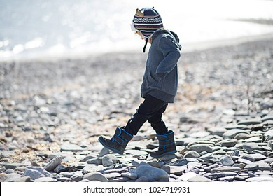 A young boy is walking on the rocky shore at the beach. He is wearing a wool winter hat and winter boots. He is stepping over the rocks at the beach. The child is happy and playful.