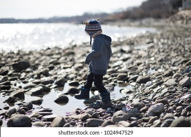 A young boy is walking over the rocks on the wet beach. It is a cold day, he is wearing a winter hat and a blue sweatshirt to stay warm. The child is having fun outside on the rocky shore at the ocean