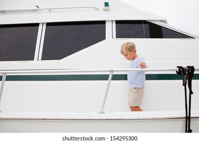 Young boy walks around outside of large yacht