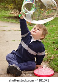 Young boy watching the huge bubble he made on wand