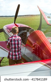 A young boy watching and learning how to fly a red aerobatic plane