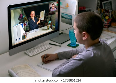 Young boy watching online class, live streaming, sitting at his desk, taking notes. Concept distance learning, home schooling, e learning, social distancing, online learning,  private lesson