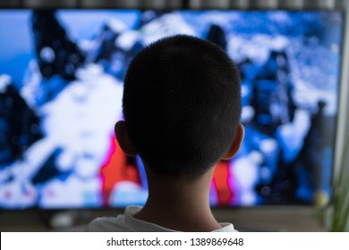 A young boy is watching a television screen with his back for a tv effect on children or a communication concept